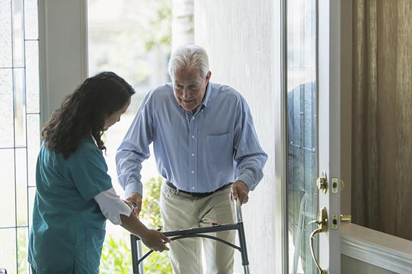 caregiver assisting senior man with walker