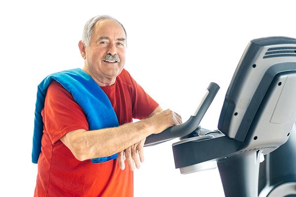 elder man leaning on exercise machine