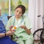 caregiver explaining medication to senior